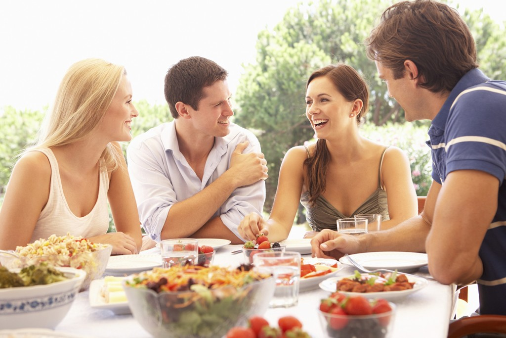 Two young couples eating outdoors